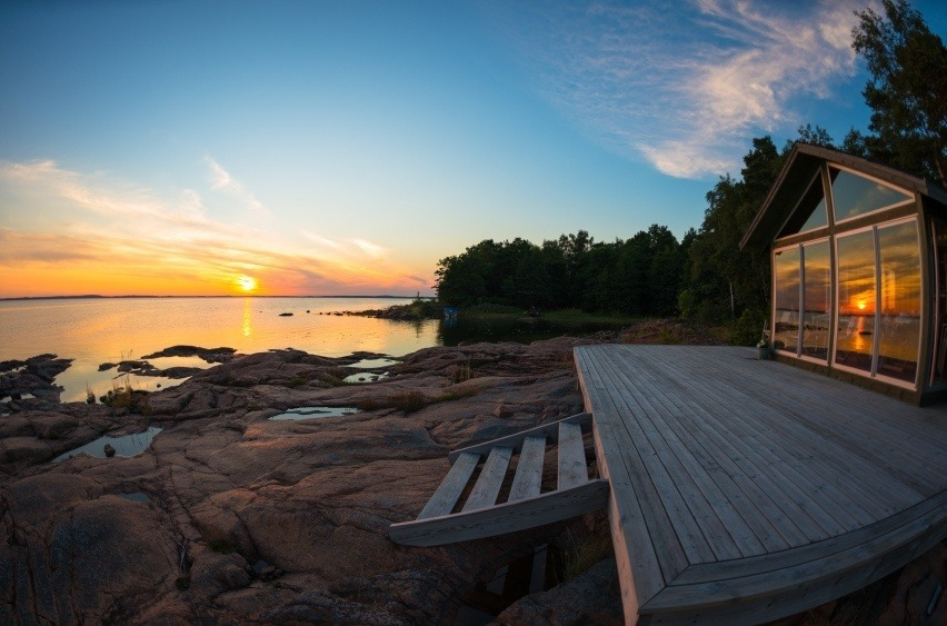 finland cottage sunset lake beach front deck lights