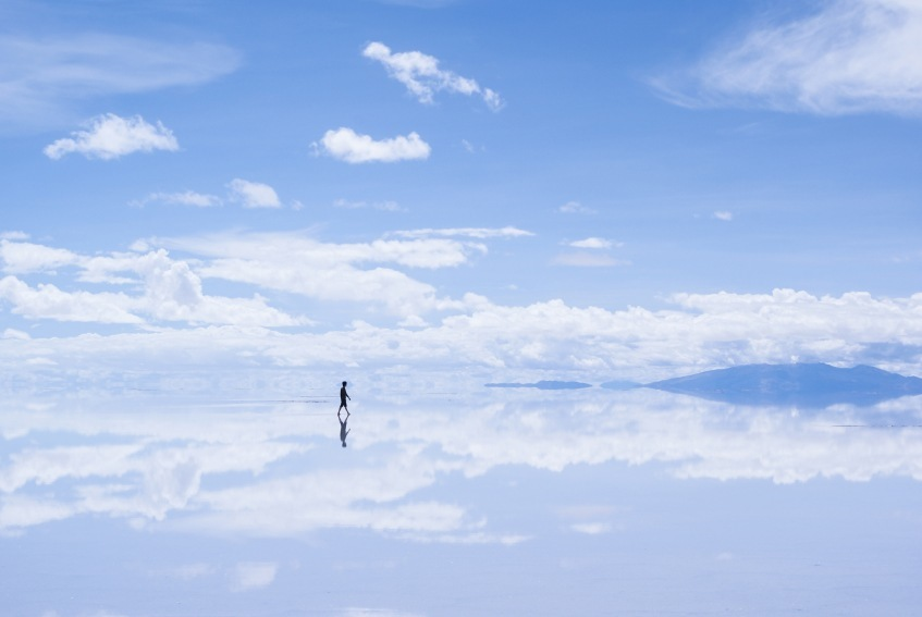 salar de uyuni bolivia person walking salt flats shimmering reflection