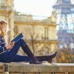 study abroad woman reading eiffel tower paris student