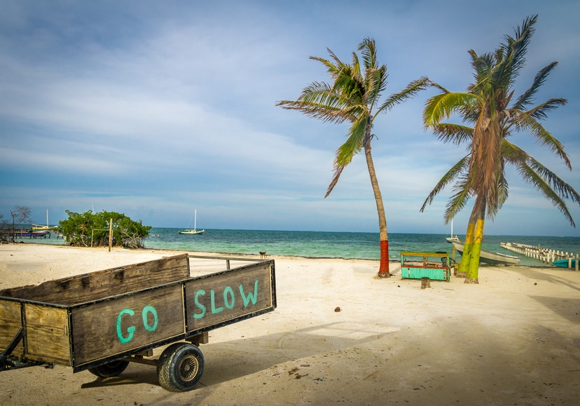 caye caulker belize go slow beach sand palm trees cart caribbean