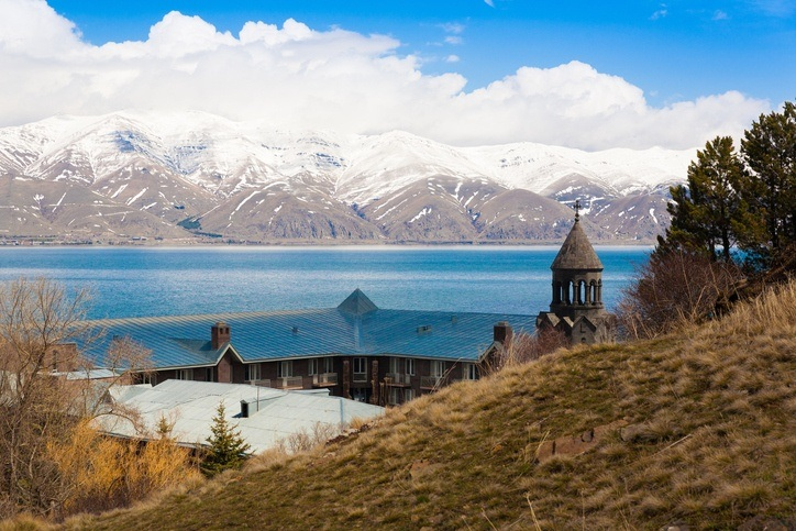 lake sevan armenia building shore mountains snow water