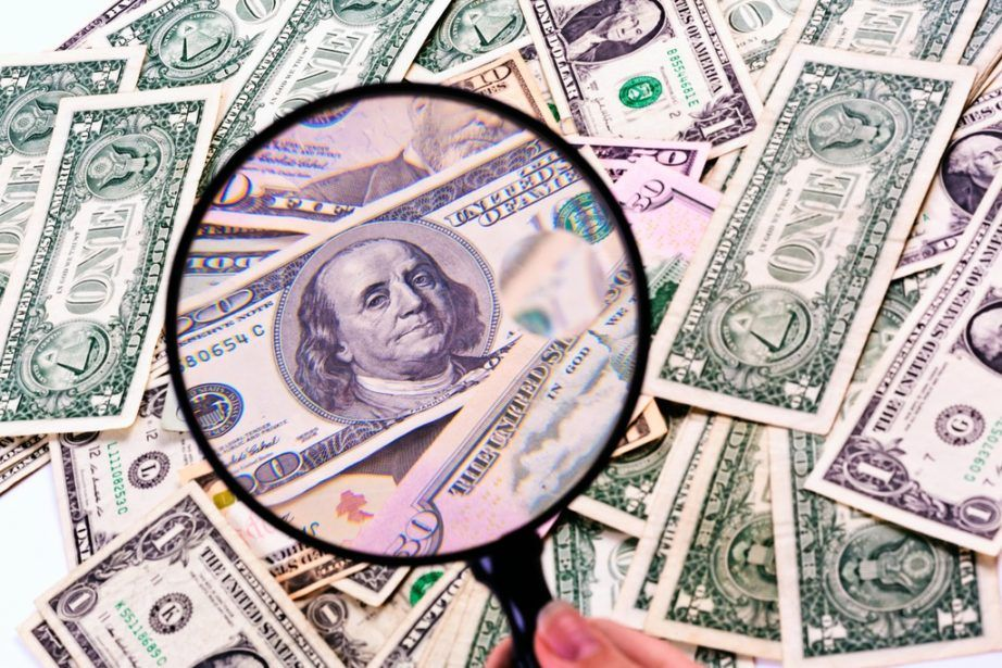 counterfeit money use us dollars magnifying glass