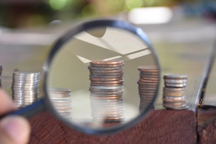magnifying glass coins stack money