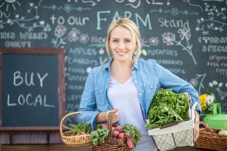 local business farmers market woman holding produce vegetables fresh